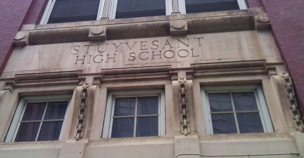 """Close-up of a stone building with """"STUYVESANT HIGH SCHOOL"""" engraved above a window"""
