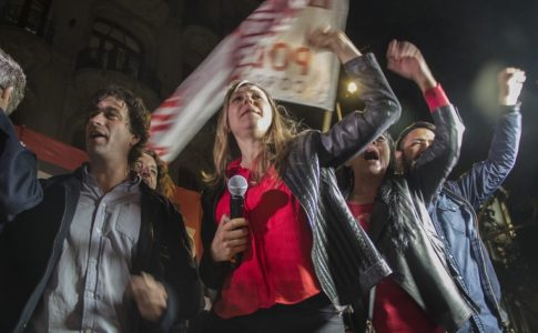 Myriam Bregman, wearing a red shirt and gray blazer, holds a microphone while raising her fist to the sky. Several other people stand behind her in similar poses. They are outside, and it is night.