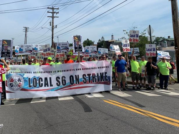 """A crowd of striking workers walks down the street on a sunny day, with those in front holding a large sign that says """"LOCAL S6 ON STRIKE."""""""