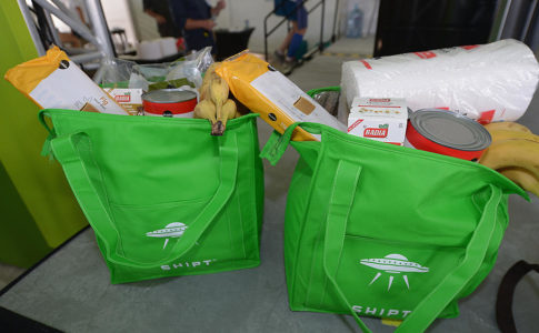 "Two bright green reusable shopping bags filled with groceries. The text on the shopping bags reads ""Shipt"" in white letters."