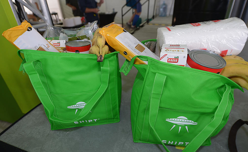 """Two bright green reusable shopping bags filled with groceries. The text on the shopping bags reads """"Shipt"""" in white letters."""