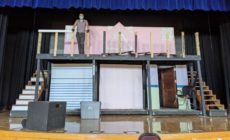 A man standing on a stage on top of theater set