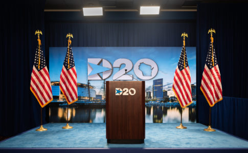 A blue stage with a brown podium in the center, flanked by 2 American flags on each side. Both the podium and the blue backdrop to the stage read D20 in white letters.