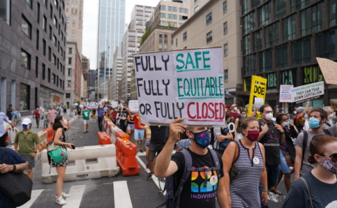 "People in a march holding a sign that says ""Fully Safe, Fully Equitable, or Fully Closed"""