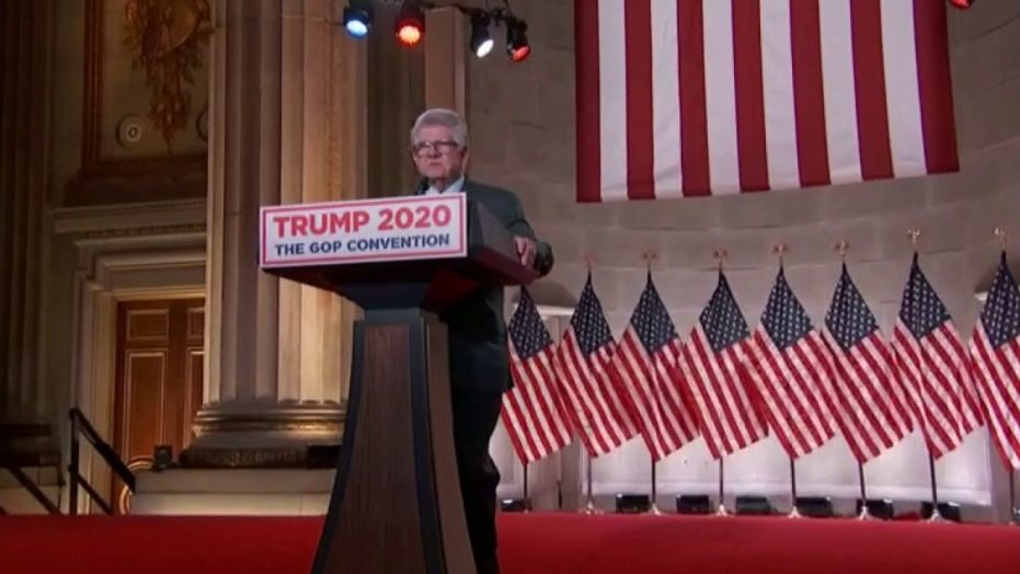 Maximo Alvarez (a graying man with a square face and square glasses) stands at a Trump 2020 podium in front of a several American flags