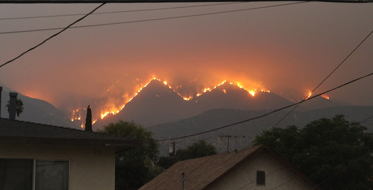 A mountain range with fires all along the top. The lighting is dark/gloomy, maybe it's evening but maybe the smoke is just making everything dark.
