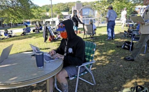 Student wearing mask and hat sits outside on laptop