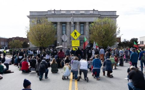 A crowd of semi-socially-distanced people kneel in the middle of a road facing away from the camera. They are facing what appears to be a gray government building with columns.