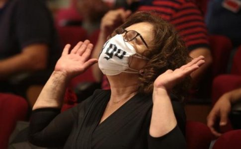 A middle aged woman with curly brown hair that falls to her chin is wearing a white mask, looking upward, and raising her hands, possibly in thanks. Other people (faces not visible) sit behind her on red auditorium-style seats.