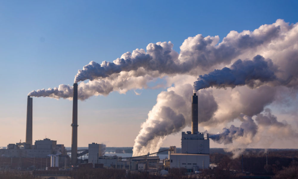 Three smokestacks spewing white-gray vapor into the air against a clear early-morning sky