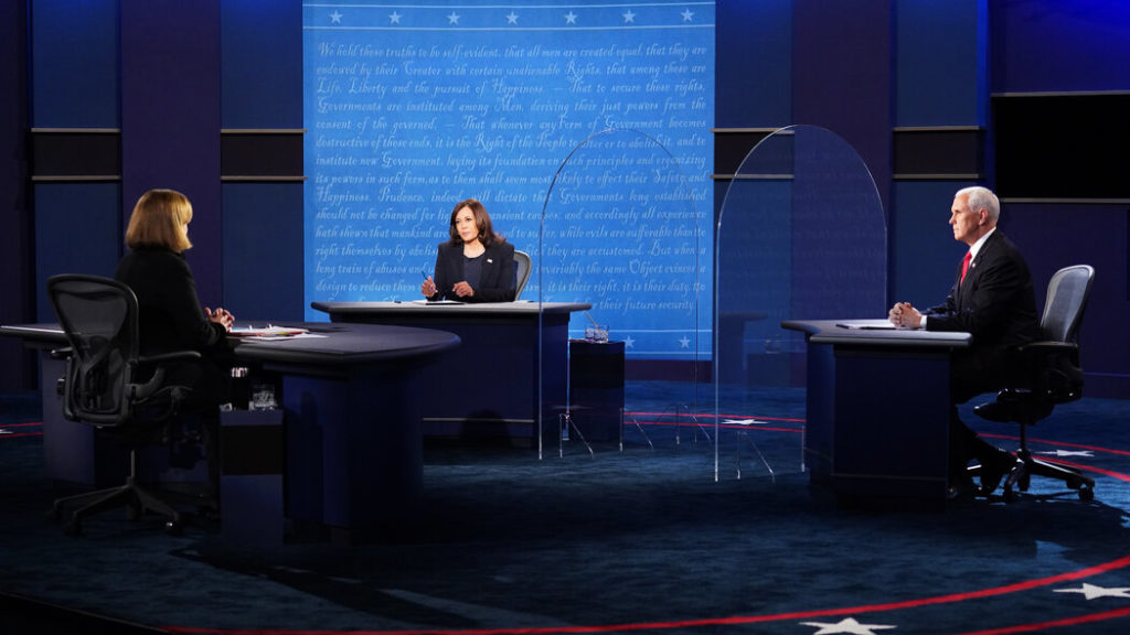 Kamala Harris and Mike Pence pictured sitting at their debate desks with short plexiglass barriers in between them