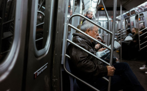 Older man sitting on the NYC Subway.