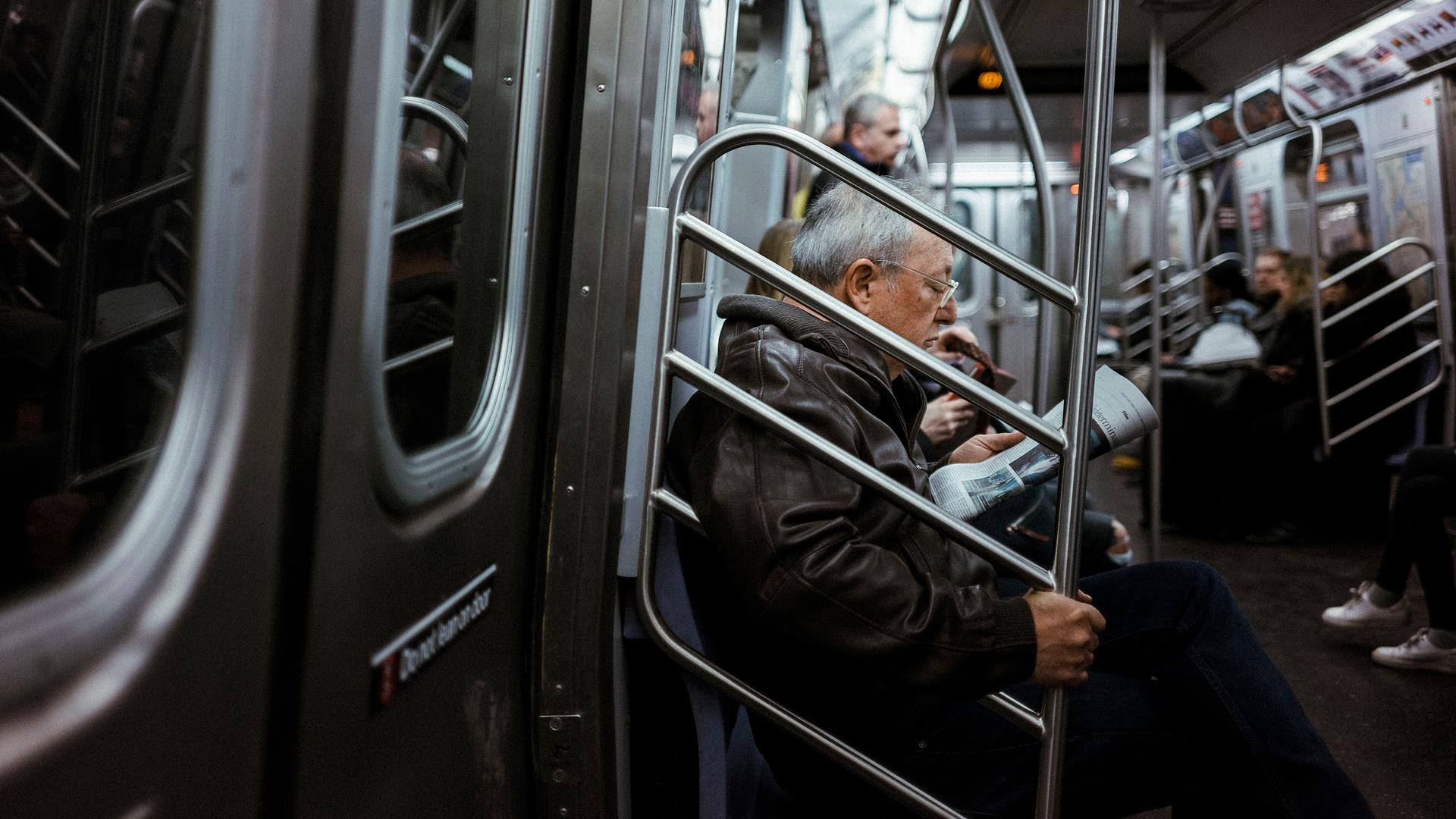 Older man sitting on the NYC Subway.