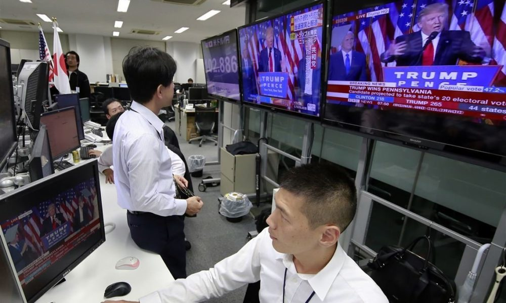 Two Japanese stock traders watch President Trump's speech on TV on Election Night 2020