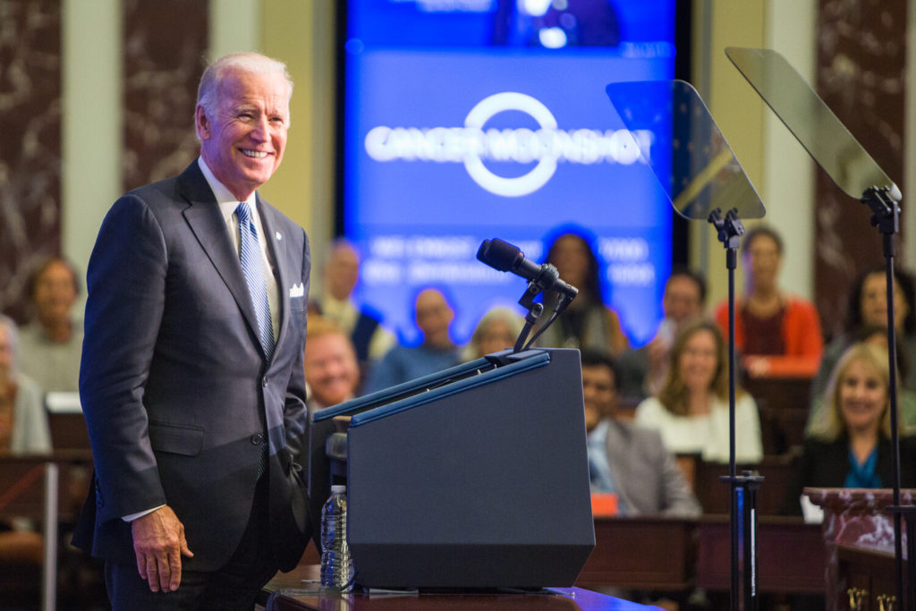 Joe Biden smiles at a crowd as he stands at a podium.
