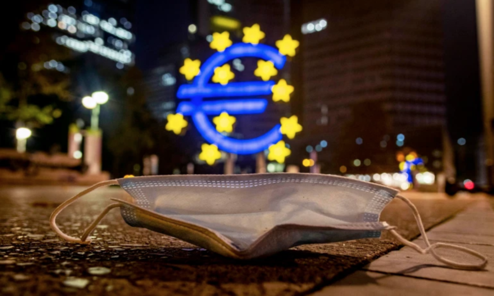 A discarded facemask in front of a large lit Euro sign in Frankfurt