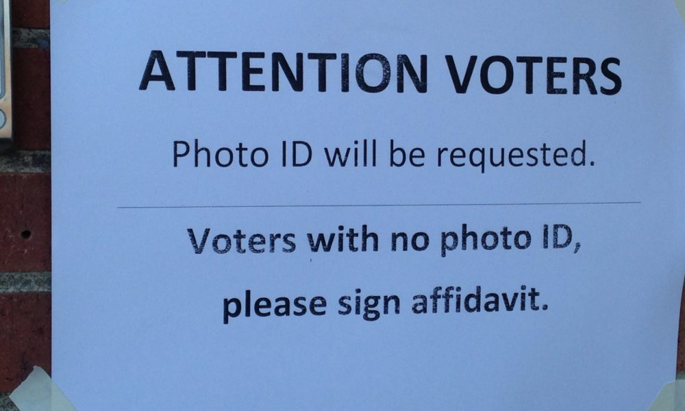 "A piece of plain white paper taped to a window reads, ""ATTENTION VOTERS: Photo ID will be requested. Voteres with no photo ID, please sign affadavit."""
