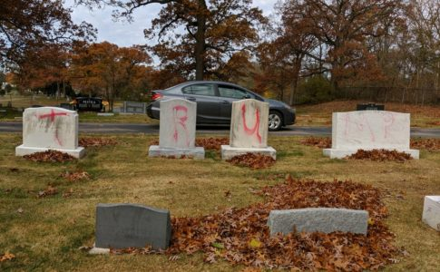 Four gravestones, with T-R-U-MP spraypainted on them in red.
