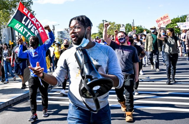 Anthony Smith holds a megaphone at the front of a march.