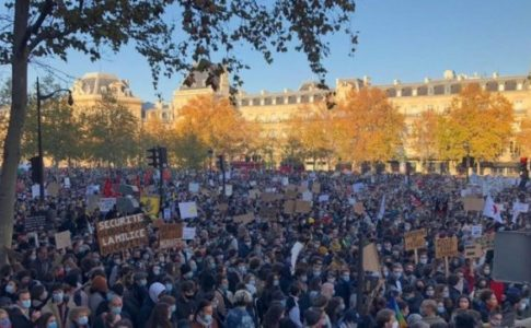 A crowd of protesters holding up signs in front of a long beige building.