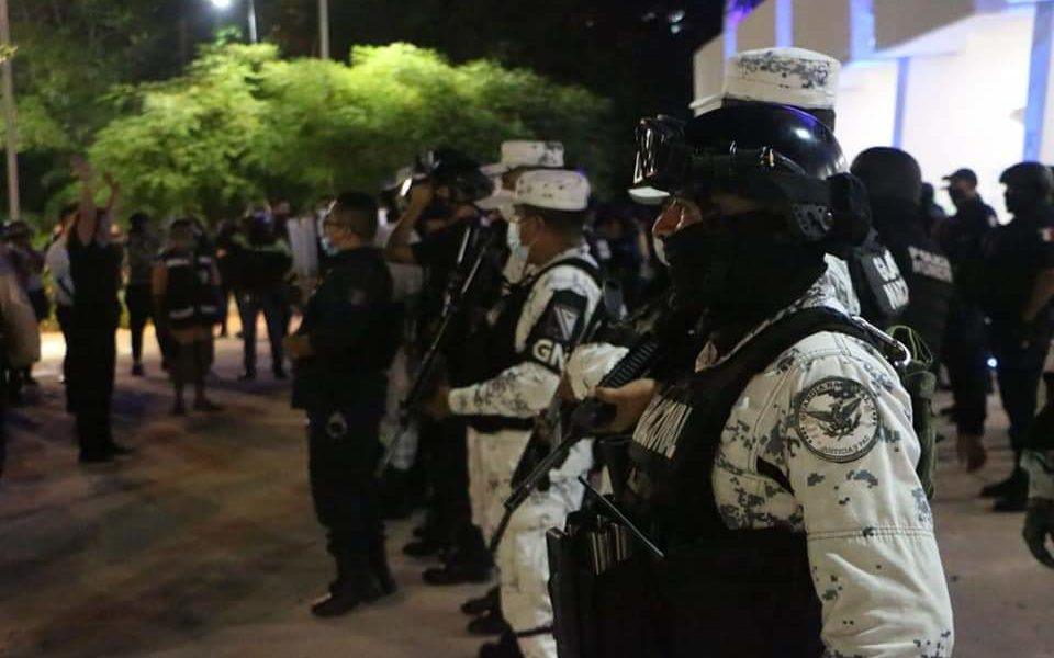 Police officers in Mexico stand heavily armed in Cancún