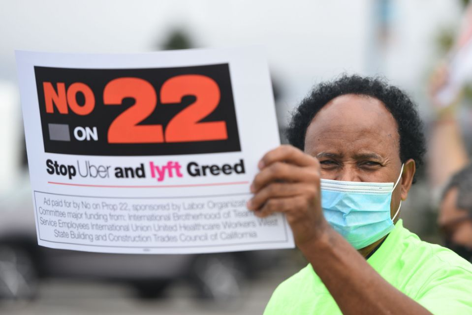 """Man holds sign that says """"No on Prop22"""""""
