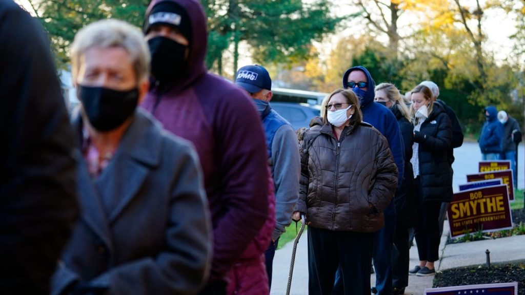 People wearing masks stand in line to vote for the 2020 election.