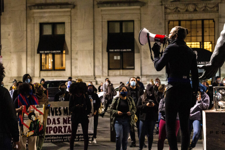 An activist leads chants through a megaphone in front of a crowd of protesters for Walter Wallace Jr. against police brutality.