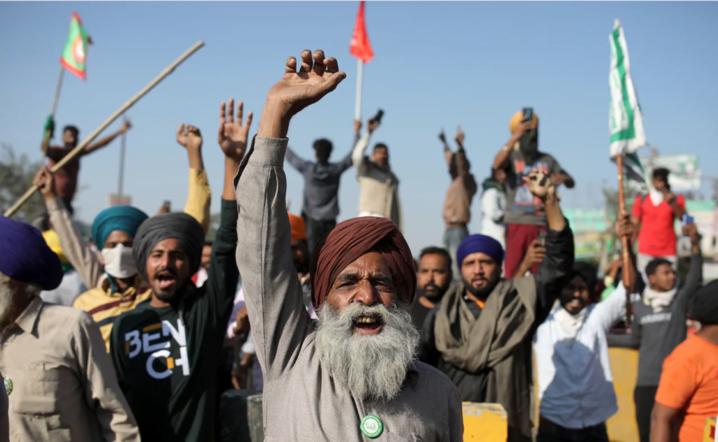 Protesters in India raise their fists.