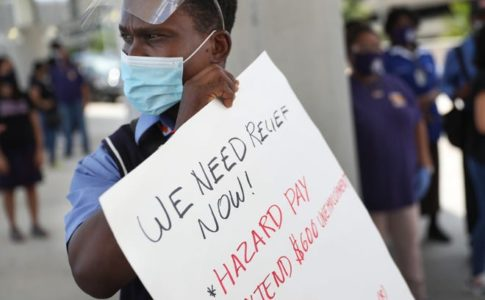 A worker holds a sign demanding hazard pay and extended benefits.