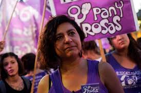 "Socialist feminist andrea d'atri wears a purple tank top and stands in front of a ""pan y rosas"" banner"