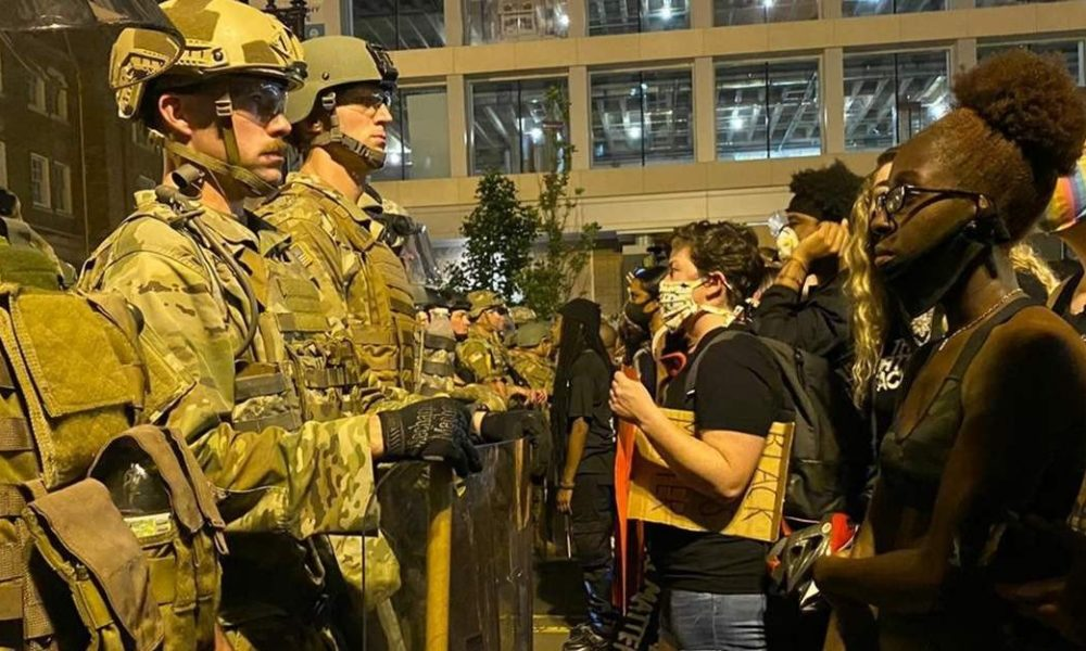 US soldiers stand uniformed wearing helmets facing protesters on the right during the BLM uprisings.