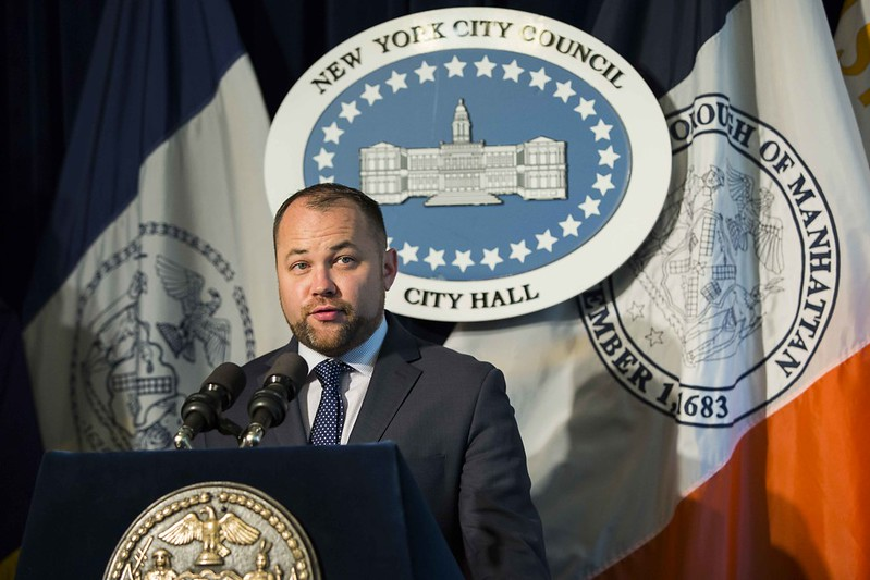 Image of Corey Booker, a white man with a beard in a black suit with a blue tie, in front of a sign that says New York City Council on top and City Hall on the bottom.