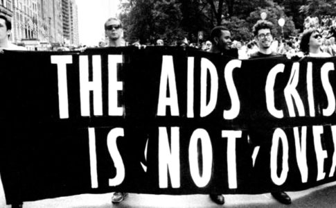 "Black and white photo of people marching with a banner that says ""The AIDS Crisis Is Not Over"""