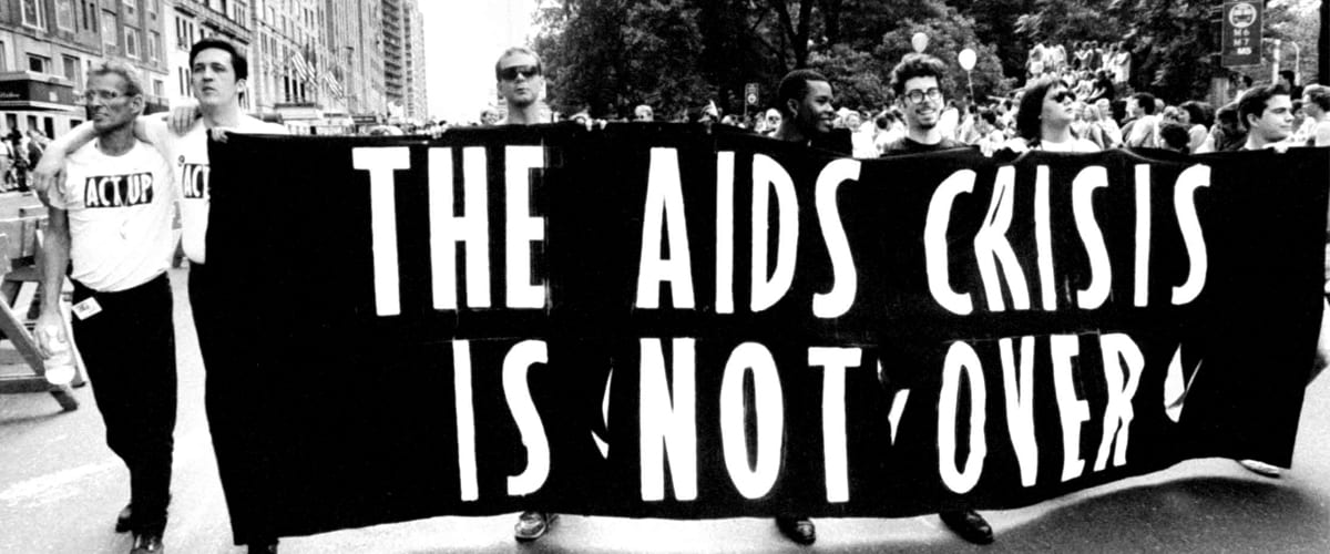 """Black and white photo of people marching with a banner that says """"The AIDS Crisis Is Not Over"""""""