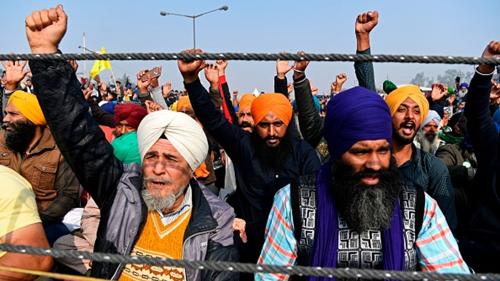Sikh protesters in India hold up their fists.