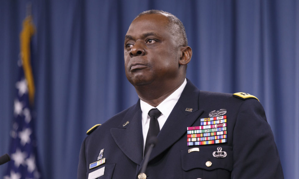 Lloyd Austin, Biden's pick to be Secretary of Defense, stands in front of a blue background and an American flag.