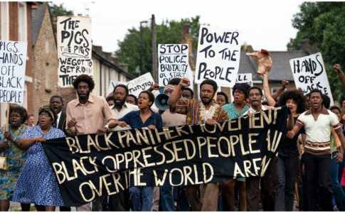 "A screenshot from the movie Mangrove. A group of around 20 Black activists march down the street on a bright but cloudy day, carrying signs in protest of police brutality. The banner at the front of the group is black with white text reading "" Black Panther Movement (line break) Black Oppressed People (word unreadable due to fold in the banner) (line break) Over the World (word unreadable due to fold in the banner)"