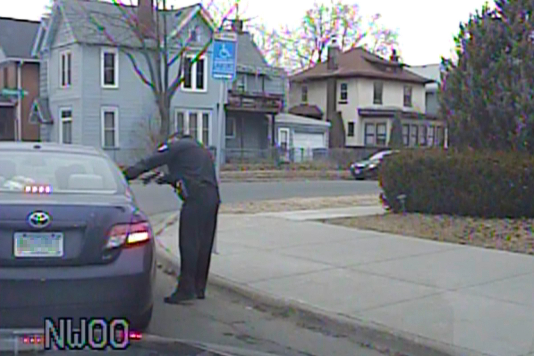 A police officer stands outside a car and points his guns at Somali teens inside in Minneapolis