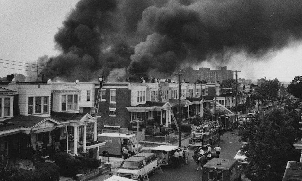 Black and white photo, a street in Philly with smoke in the distance due to the MOVE bombing.
