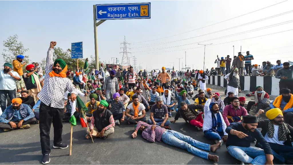 Protesters in India sit blocking the road