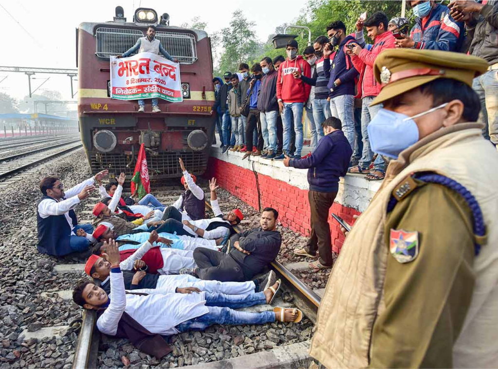 Protesters in India lay on train tracks in front of train, other protesters look from platform above.