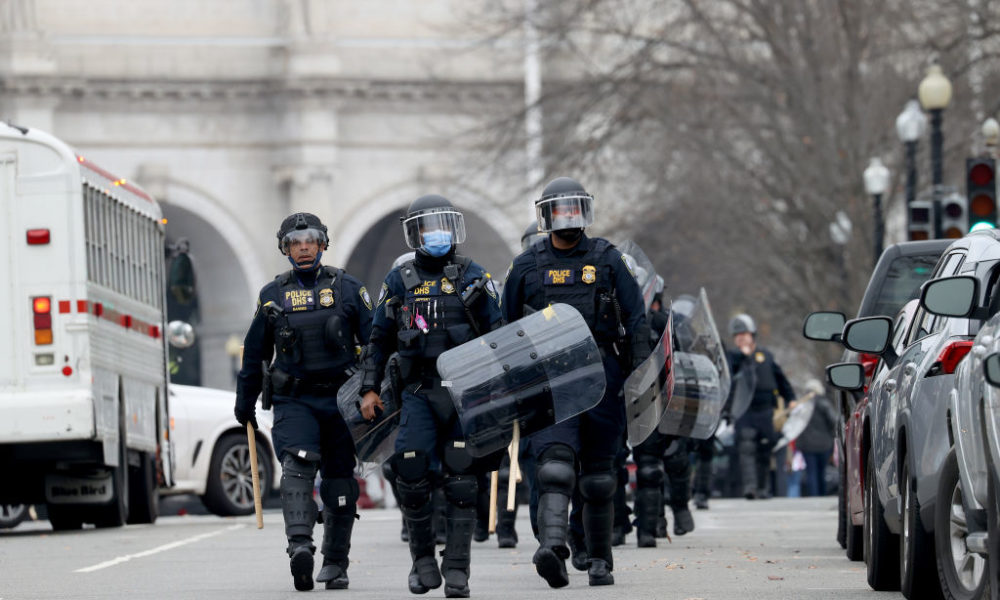 Police in riot gear and shields near Washington Capitol.