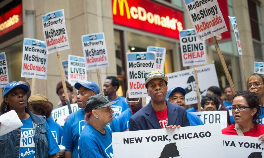 "Fast Food workers hold sign that read: ""New York. Chicago $15"""