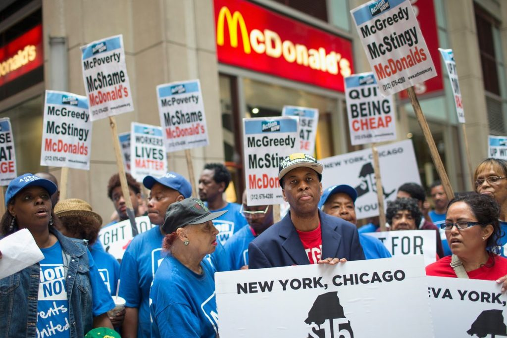 """Fast Food workers hold sign that read: """"New York. Chicago $15"""""""