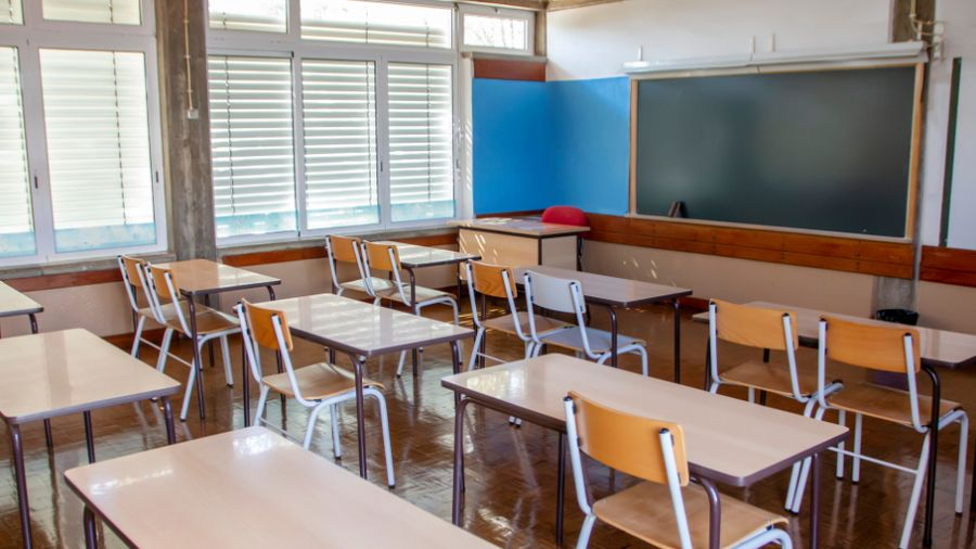 The photograph depicts an empty school classroom.