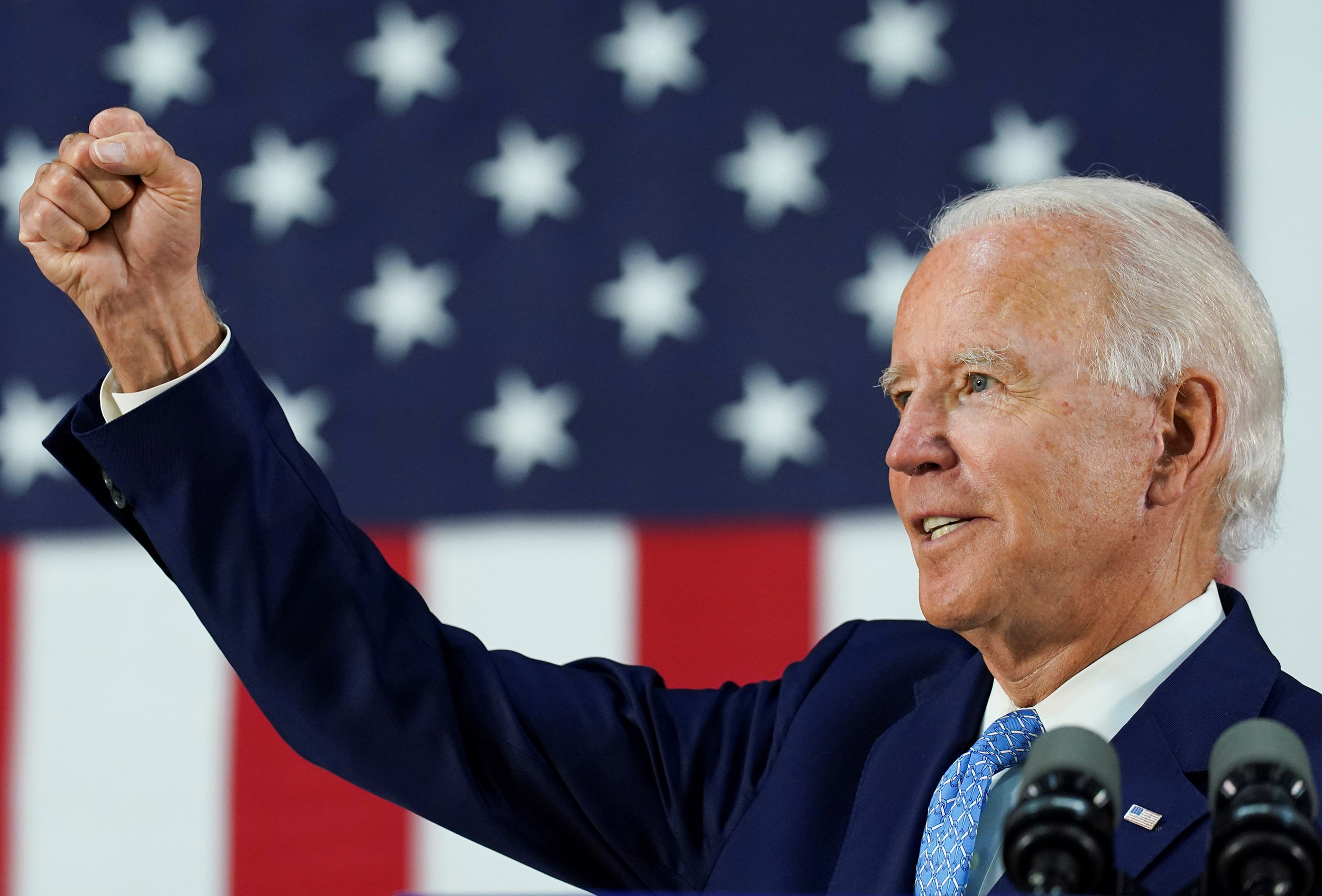 President-Elect Joe Biden stands in front of an American flag, looking to the left, with his right fist raised.