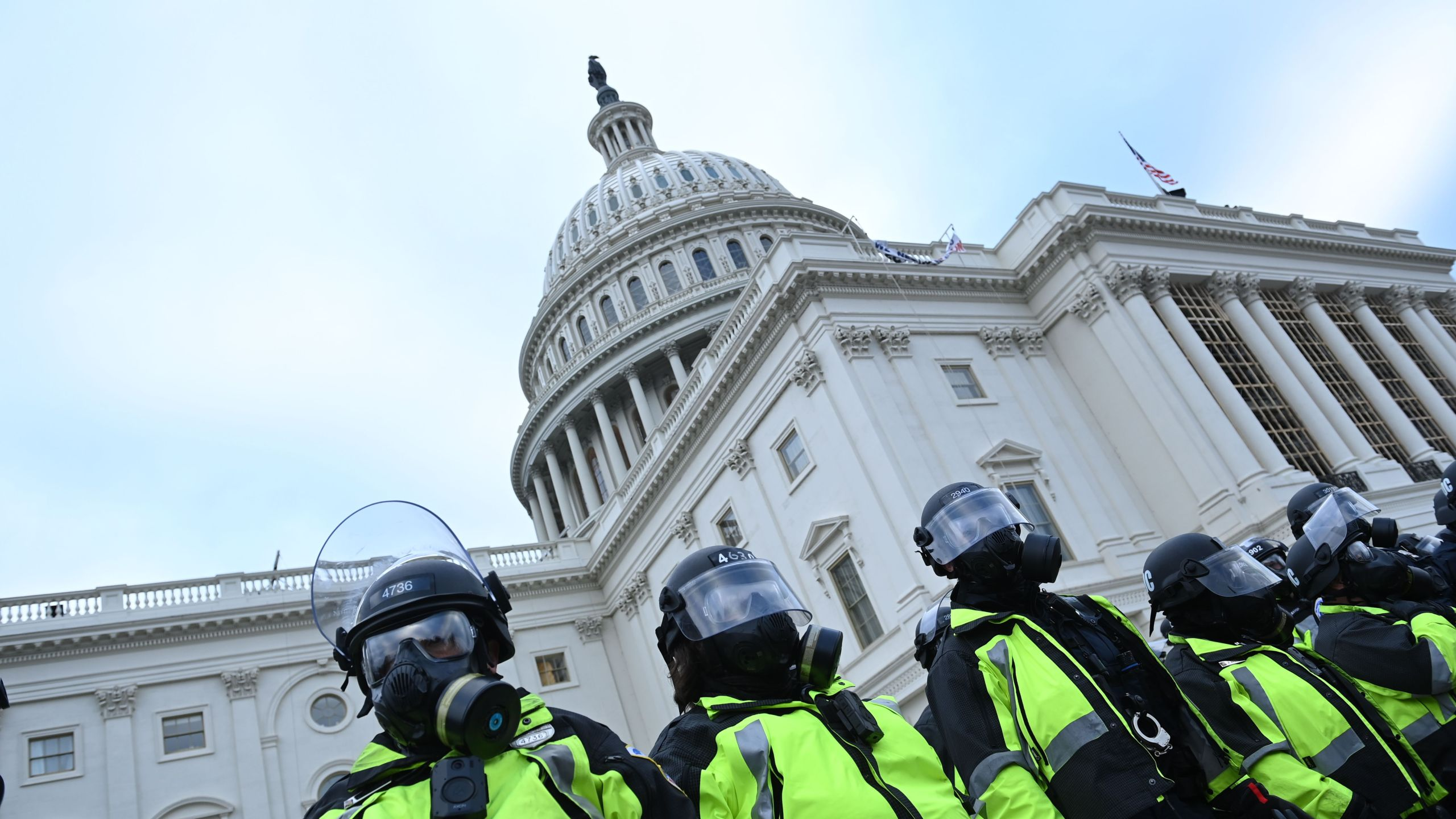 Police in neon yellow vests and shielded helmets stand outside Capitol building.