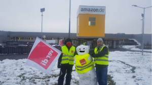 Two German Amazon workers including Christian Krähling stand beside a snowman, all are wearing high-visibility vests.