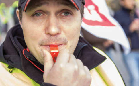 German Amazon Worker Christian Krähling blows a whistle while looking into the camera